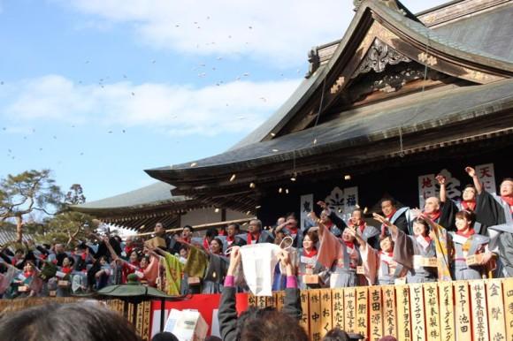 中尊寺の大節分会で紙袋で豆を取ろうとする人