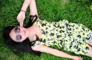 サングラスの中国人女性が草の上で寝転がる