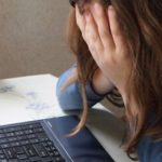 パソコンの前で顔を覆う女性